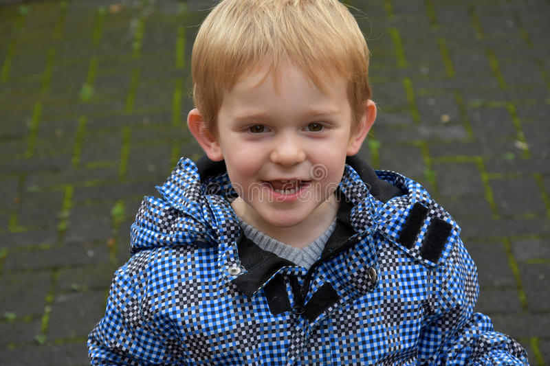 Toddler boy. Portrait of a mischievously toddler boy with blond hair royalty free stock image