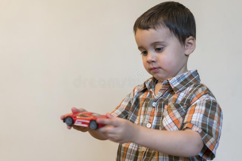Toddler boy with a red toy car. copy space.  stock photo