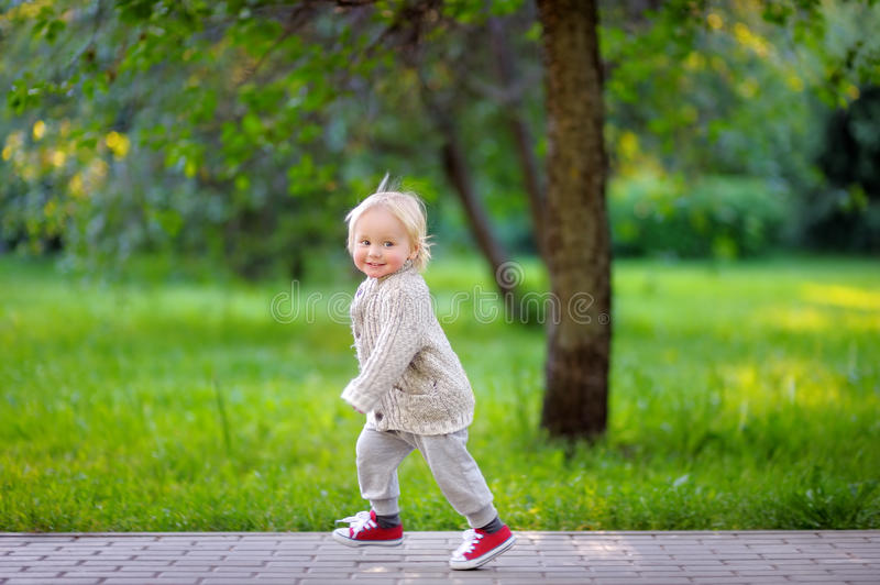 Toddler boy running in the park royalty free stock photo