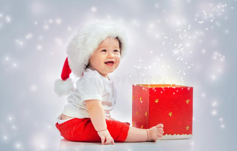 Toddler boy with santa hat opening a gift box stock image