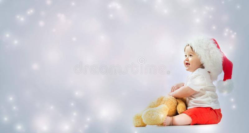 Toddler boy with santa hat playing with his teddy bear royalty free stock image