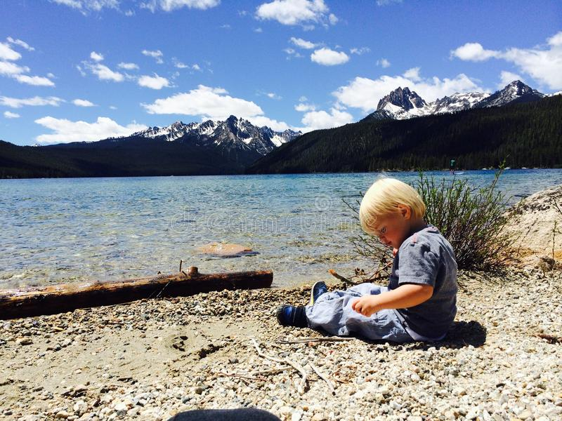Toddler Boy sits at the Edge of Red Fish Lake, Skipping Rocks. Little blonde toddler boy sits at the edge of Red Fish Lake, skipping rocks in the crystal clear royalty free stock images