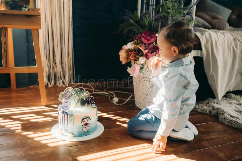 Toddler boy sits on floor near birthday cake. On background of flowers royalty free stock photos