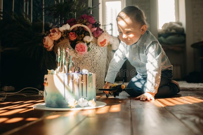 Toddler boy sits on floor near birthday cake. On background of flowers royalty free stock photo