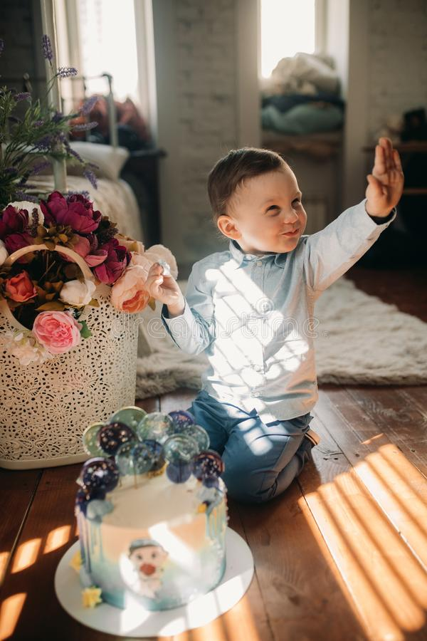 Toddler boy sits on floor near birthday cake. On background of flowers stock photography