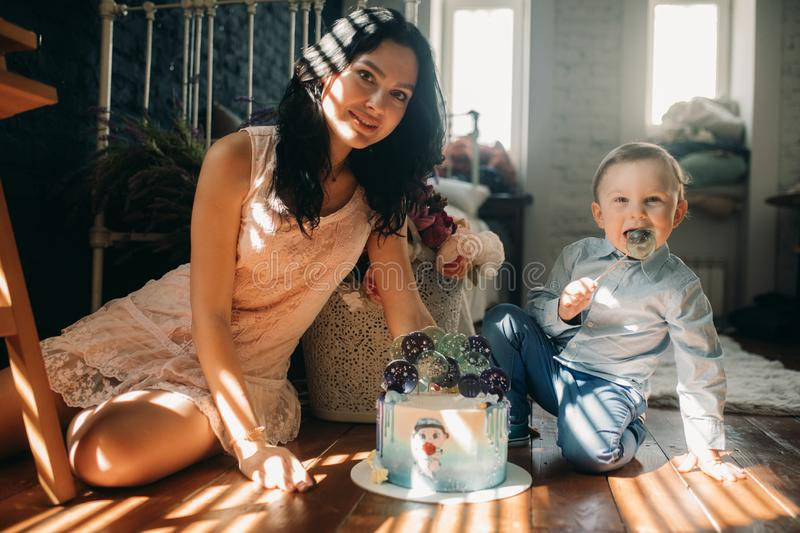 Toddler boy sits with his mother near birthday cake. Toddler boy sits on floor with his mother near birthday cake on background of flowers stock photo