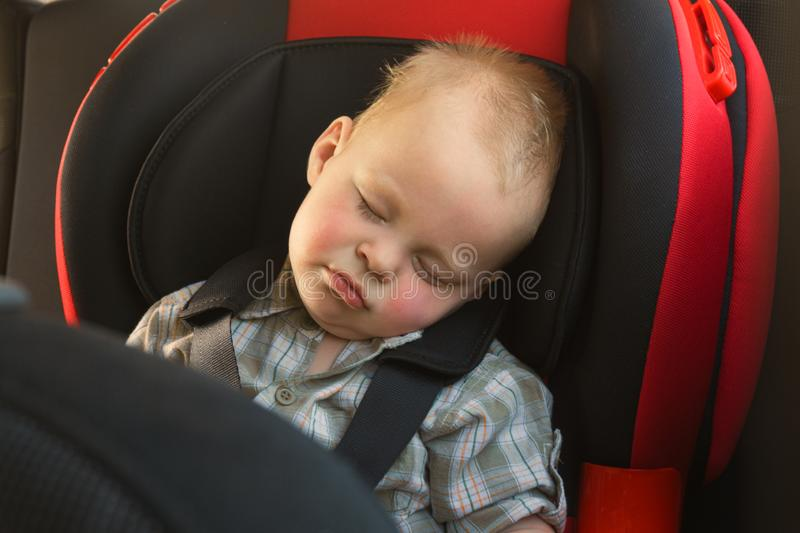 Toddler boy sleeps peacefully and safe while secured with seat belts in the car. stock photography