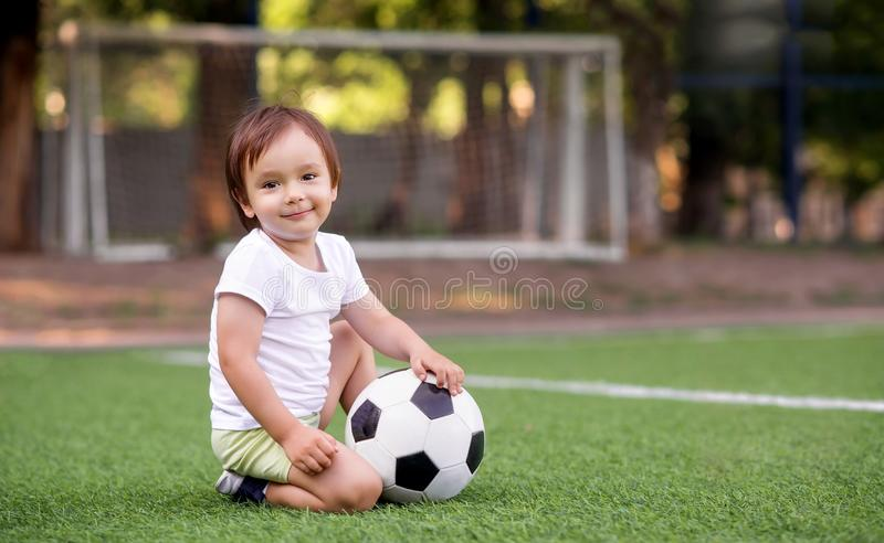 Toddler boy in sports uniform sitting with soccer ball at football field outdoors in summer day. Goalposts soccer nets in royalty free stock photos
