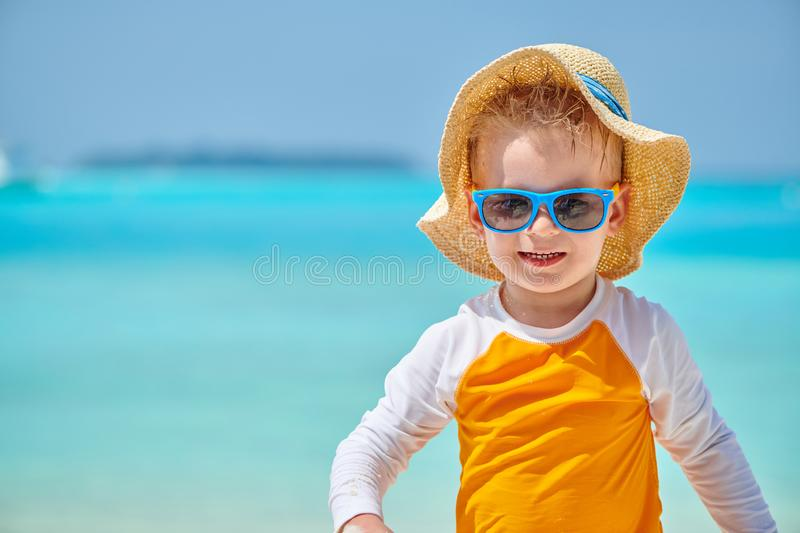 Toddler boy with sunglasses on beach royalty free stock images