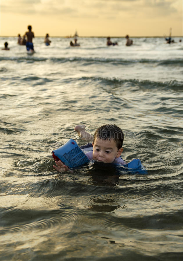 Toddler boy swimming in the ocean stock images