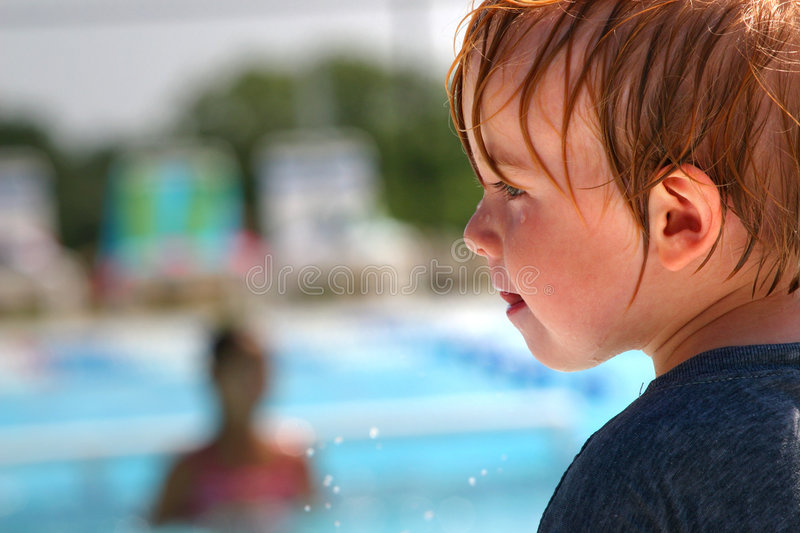 Toddler boy at swimming pool. Closeup of wet boy at a swimming pool wearing a shirt to protect himself from the sun royalty free stock images