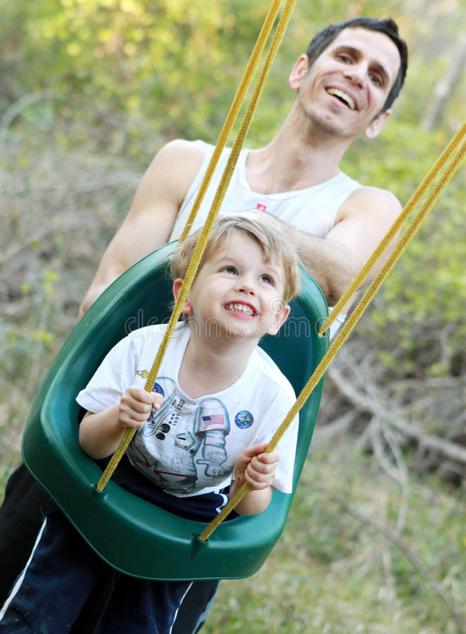 Toddler boy on a swing stock photo