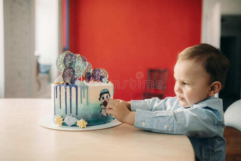 Toddler boy touches cake for birthday by his hands. Toddler boy touches cake for birthday on the table by his hands stock image