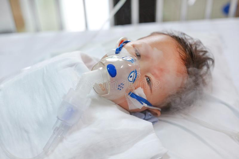 Toddler boy using nebulizer to cure asthma or pneumonia disease . Sick baby boy rest on patients bed and has inhalation therapy by. The mask of inhaler royalty free stock images