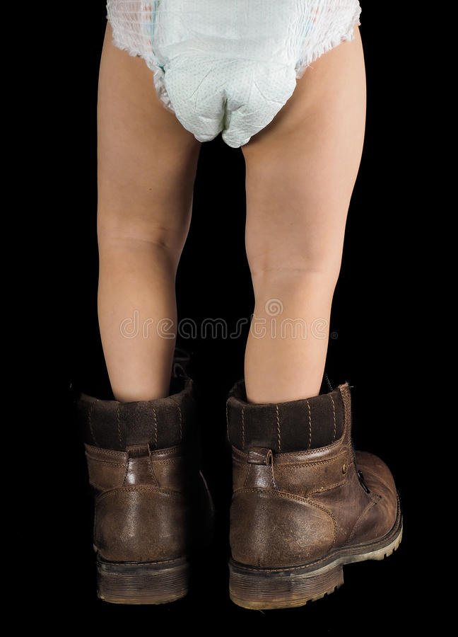 Toddler boy, walking away towards black background in too big boots. Toddler boy in diapers, walking away towards black background in fathers brown leather boots stock photos