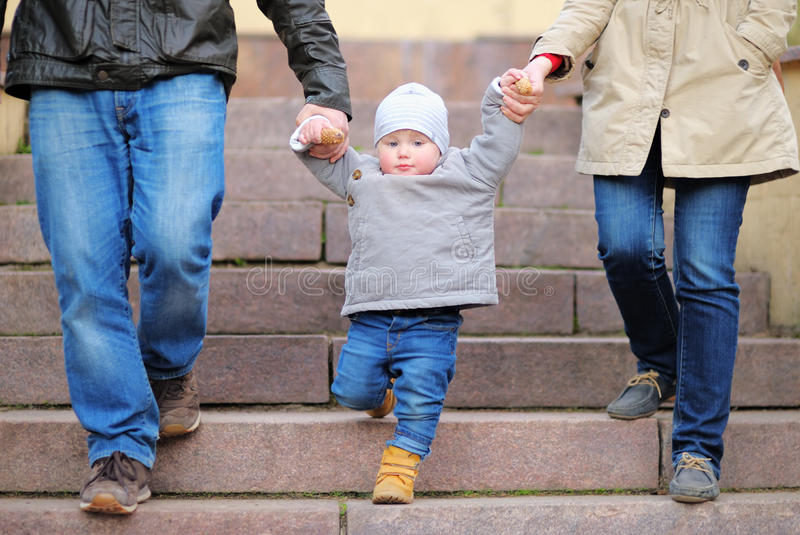 Toddler boy walking with his parents. Close up photo of beautiful toddler boy walking with his parents royalty free stock images