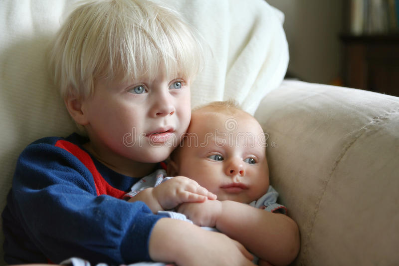 Toddler Brother Holding Baby Sister on Couch. A toddler big brother is holding and hugging his baby sister as they sit on the couch in their home watching royalty free stock image