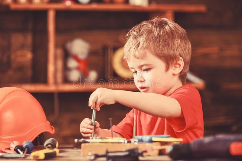 Toddler on busy face plays with bolts at home in workshop. Kid boy play as handyman. Handcrafting concept. Child cute royalty free stock photography