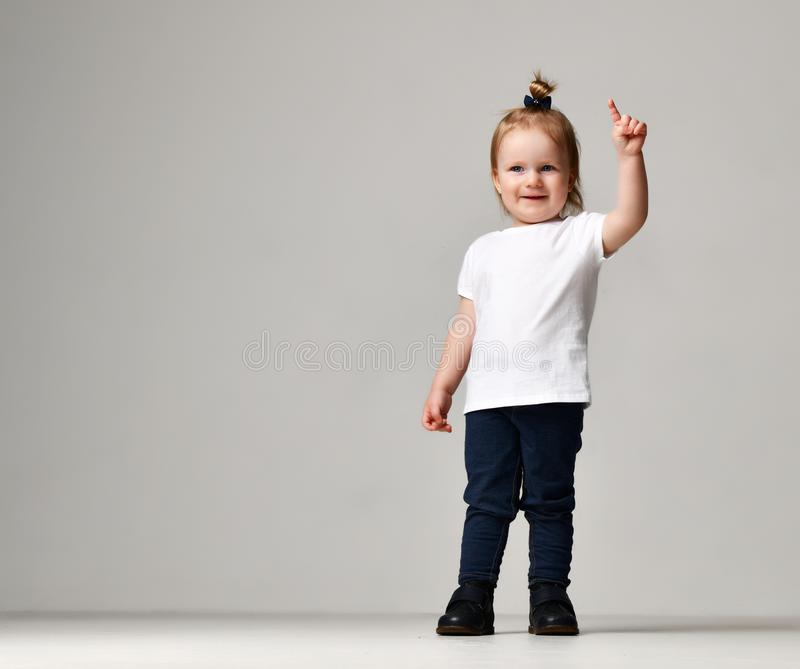 Toddler child baby girl kid standing in white free text space t-shirt pointing finger up. On grey background royalty free stock photography