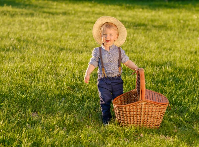Toddler child outdoors. One year old baby boy wearing straw hat with picnic basket stock images