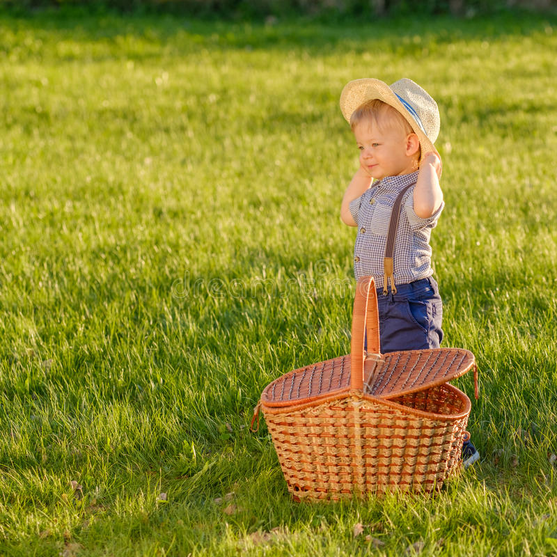 Toddler child outdoors. One year old baby boy wearing straw hat with picnic basket stock photography