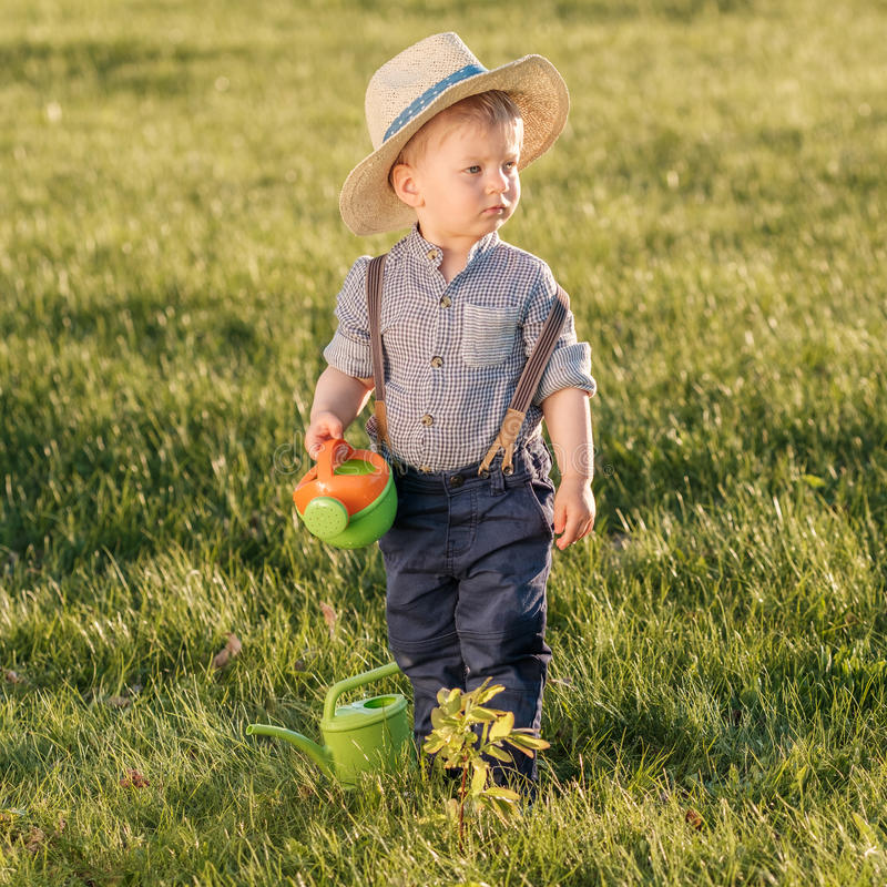 Toddler child outdoors. One year old baby boy wearing straw hat using watering can royalty free stock photo