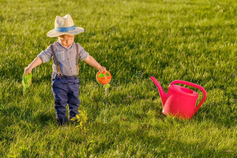 Toddler child outdoors. One year old baby boy wearing straw hat using watering can royalty free stock photography