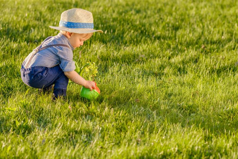 Toddler child outdoors. One year old baby boy wearing straw hat using watering can stock photography