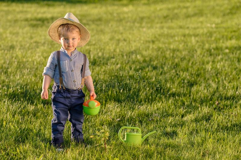 Toddler child outdoors. One year old baby boy wearing straw hat using watering can stock image