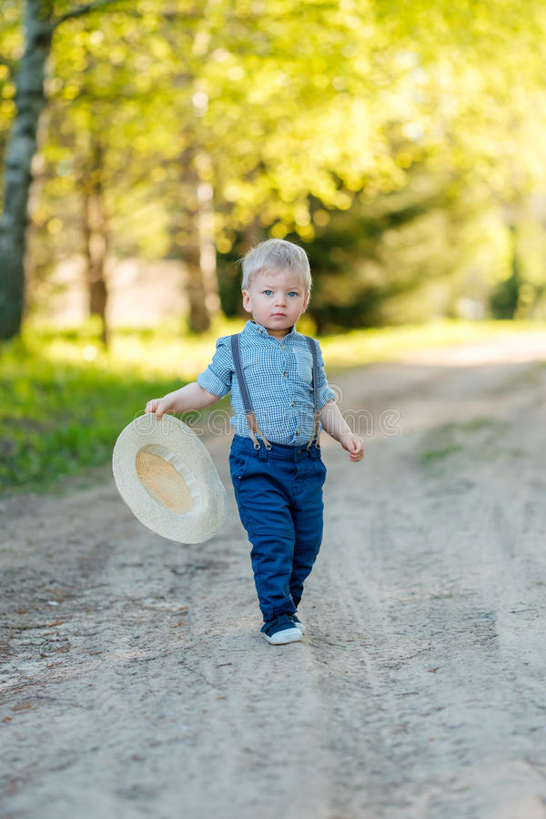 Toddler child outdoors. Rural scene with one year old baby boy with straw hat stock images
