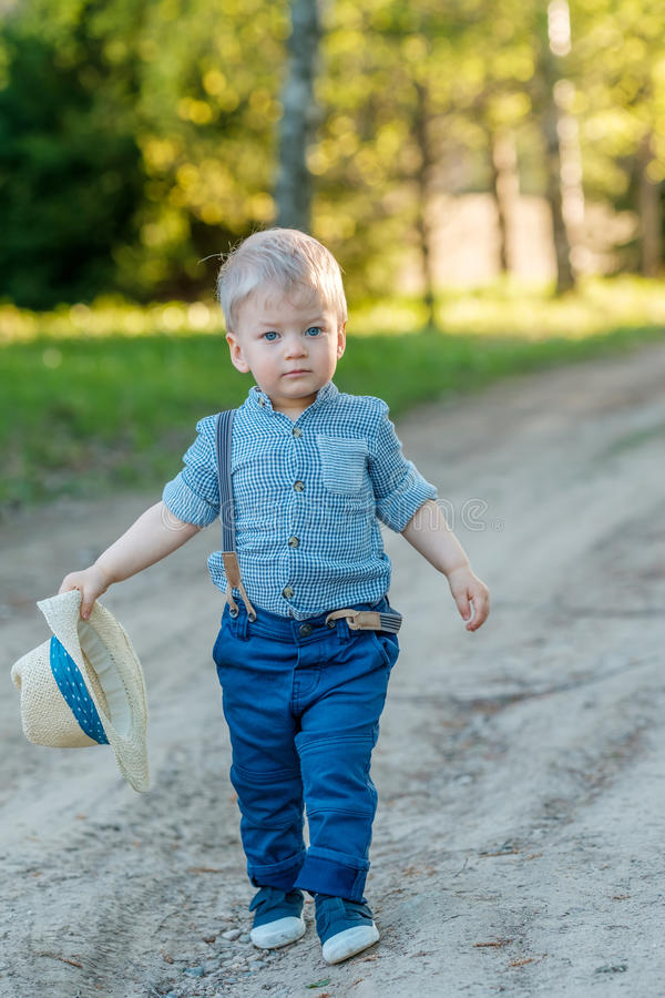 Toddler child outdoors. Rural scene with one year old baby boy with straw hat stock photography