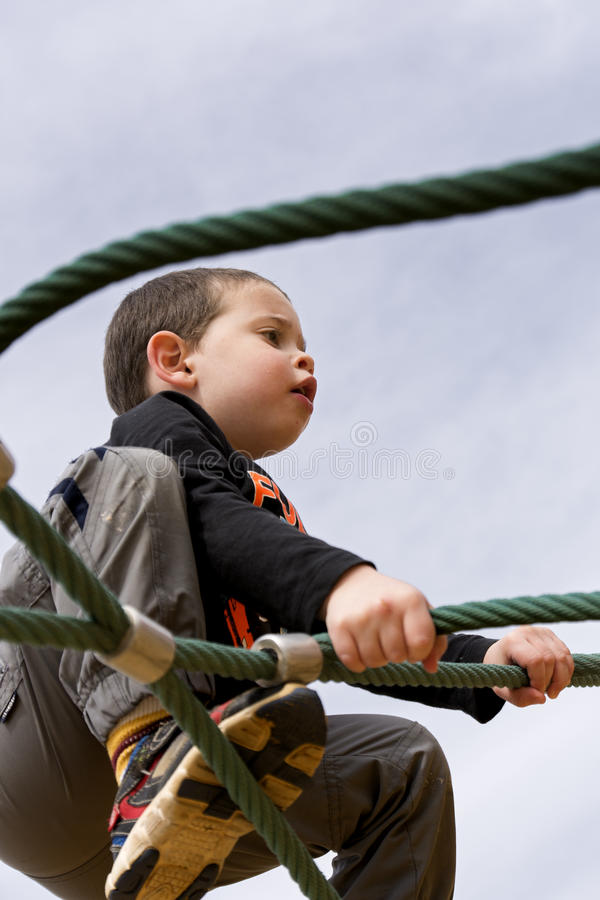 Toddler climbing a rope facility stock image