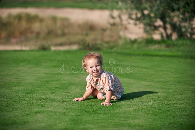 Toddler crawling at the green golf course at sunny day stock photo