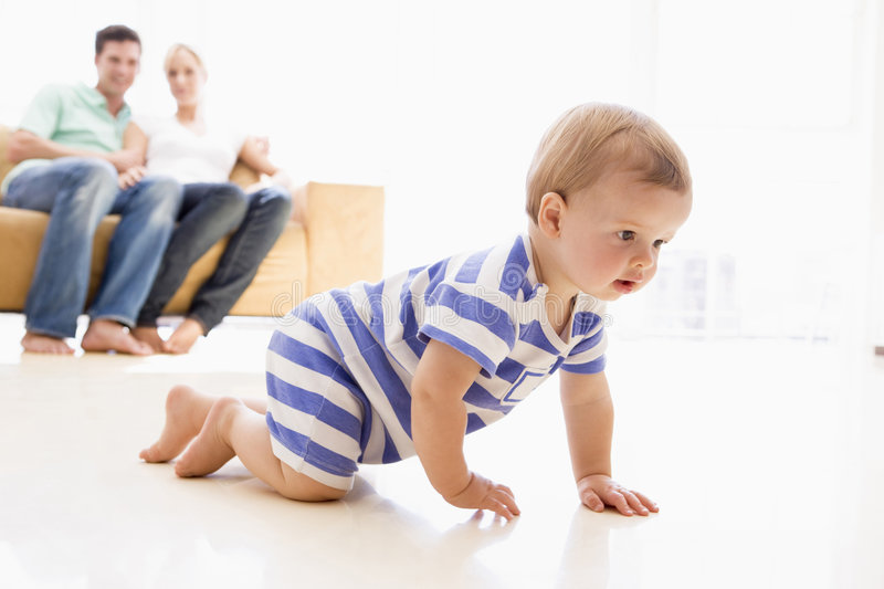 Toddler crawling with parents in background royalty free stock photo