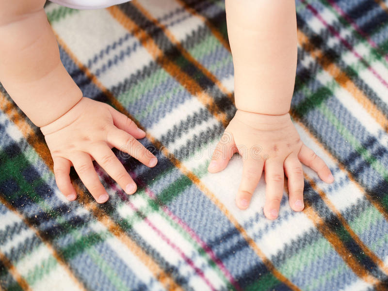 Toddler crawling on picnic blanket. Toddler crawling on a picnic blanket. Baby hands close-up stock images
