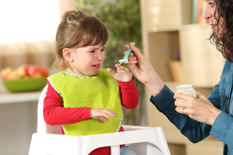 Toddler crying at lunch time stock photos