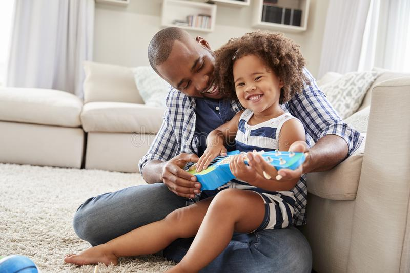 Toddler daughter sits on dad�s knee playing ukulele at home stock photo