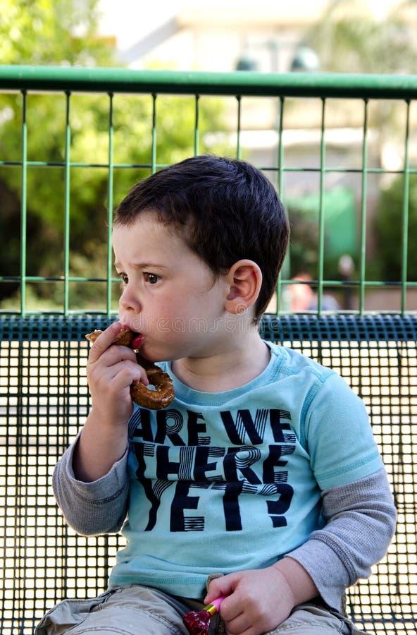 Toddler eating a pretzel royalty free stock photos