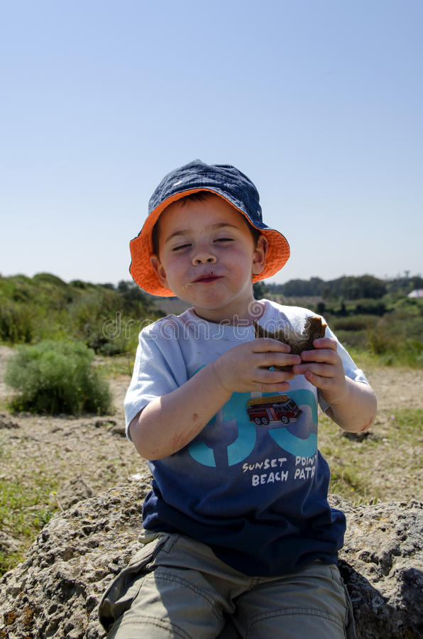 Toddler eating a sandwich at nature reserve stock image