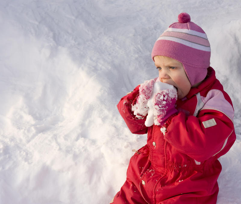 Toddler eating snow stock photography