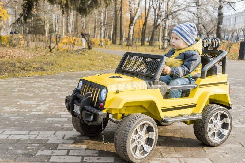 Toddler em amarelo dirige carro com motor elétrico no outono Park imagem de stock