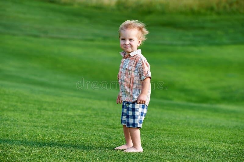 Toddler em pé no campo de golfe verde no dia ensolarado imagem de stock