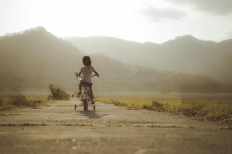 Toddler enjoy riding her bicycle outdoor stock photos