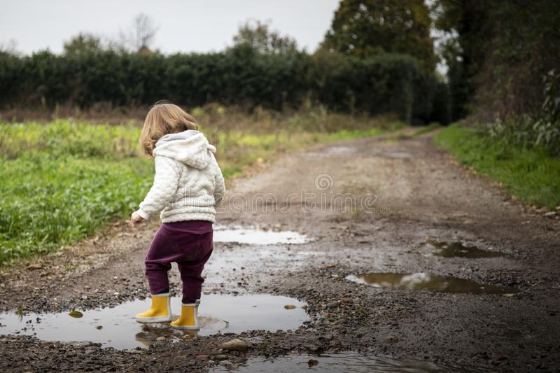 Toddler splashing in puddles in muddy country road stock images