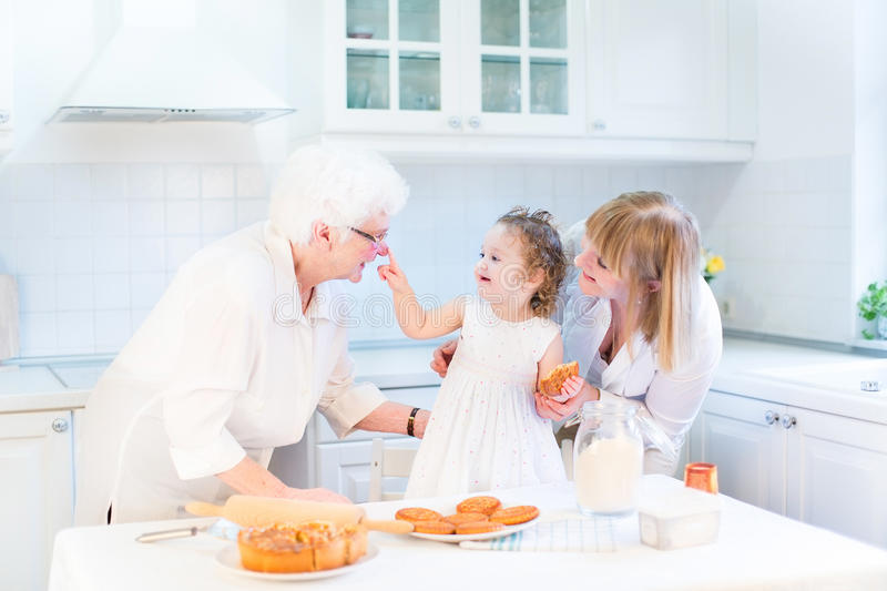 Toddler girl baking an apple pie with grandmothers. Happy funny toddler girl playing in a white beautiful kitchen baking an apple pie with her grandmothers stock images