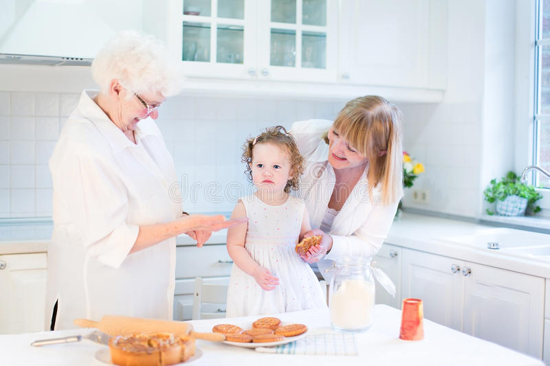 Toddler girl baking apple pie with her grandmothers stock photography