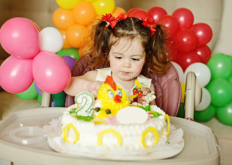 Toddler girl with birthday cake. Cute toddler girl with her birthday cake royalty free stock images