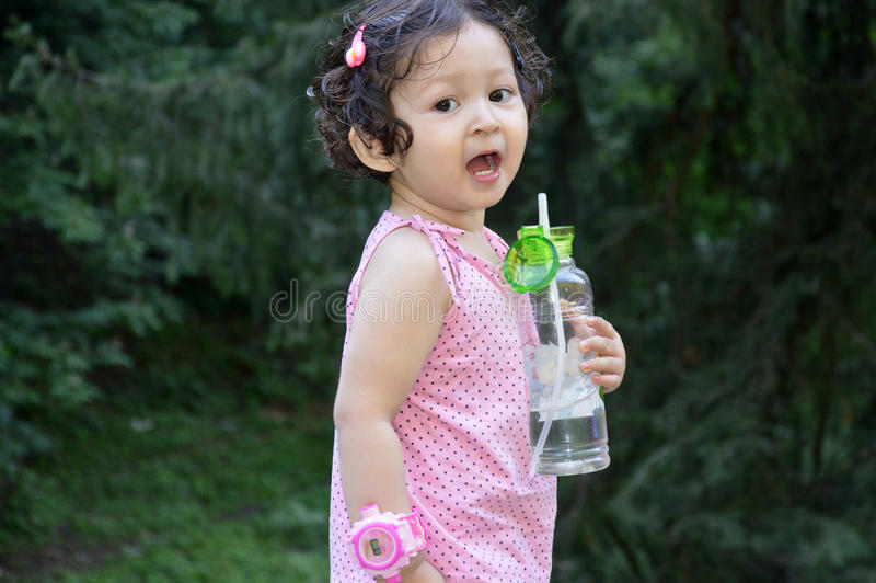 Toddler girl with bottle of water royalty free stock images