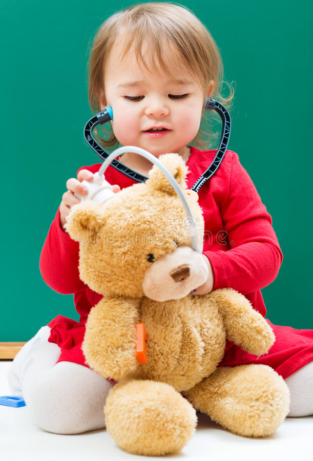 Toddler girl caring for her teddy bear with a stethoscope royalty free stock image