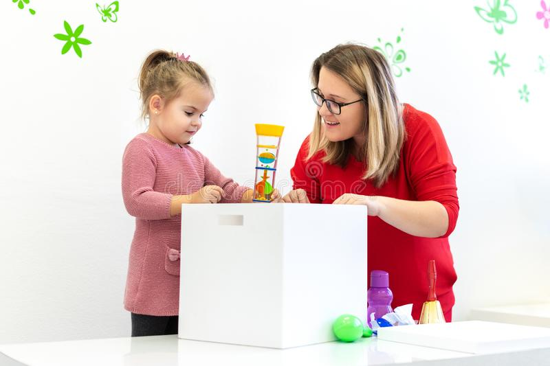 Toddler girl in child occupational therapy session doing sensory playful exercises with her therapist. Toddler girl in child occupational therapy session doing stock photography